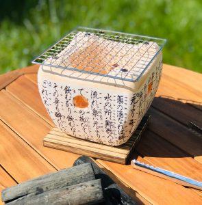 Barbecue japonais daimyo posé sur une table de jardin avec charbon binchotan