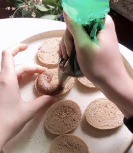 pochage de ganache praliné et miso dans des coques de macarons aux noisettes