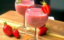 deux verre à pied avec lassi à la fraise sur une planche à découper en bois