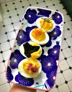 oeufs mimosa à la mayonnaise japonaise au yuzu sur une assiette bleu et carrelage blanc et noir