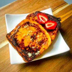 deux tranches de brioche perdue à la kinako avec fraise sur assiette blanche et planche en bois