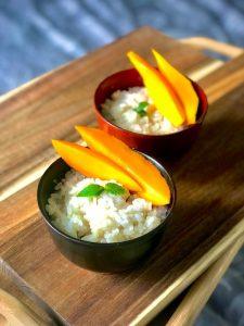 deux bols de riz au lait de coco avec mangue sur une planche en bois