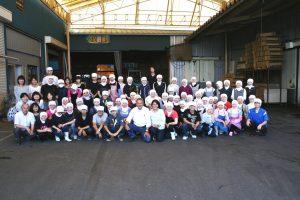 employés de kashiwazaki seika accroupis devant l'usine au japon