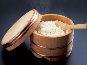 riz japonais dans un seau pour riz à sushi avec couvercle et cuillère en bois