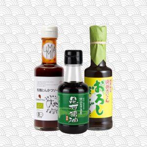 trois bouteilles de sauces japonaises sur fond à motif japonais